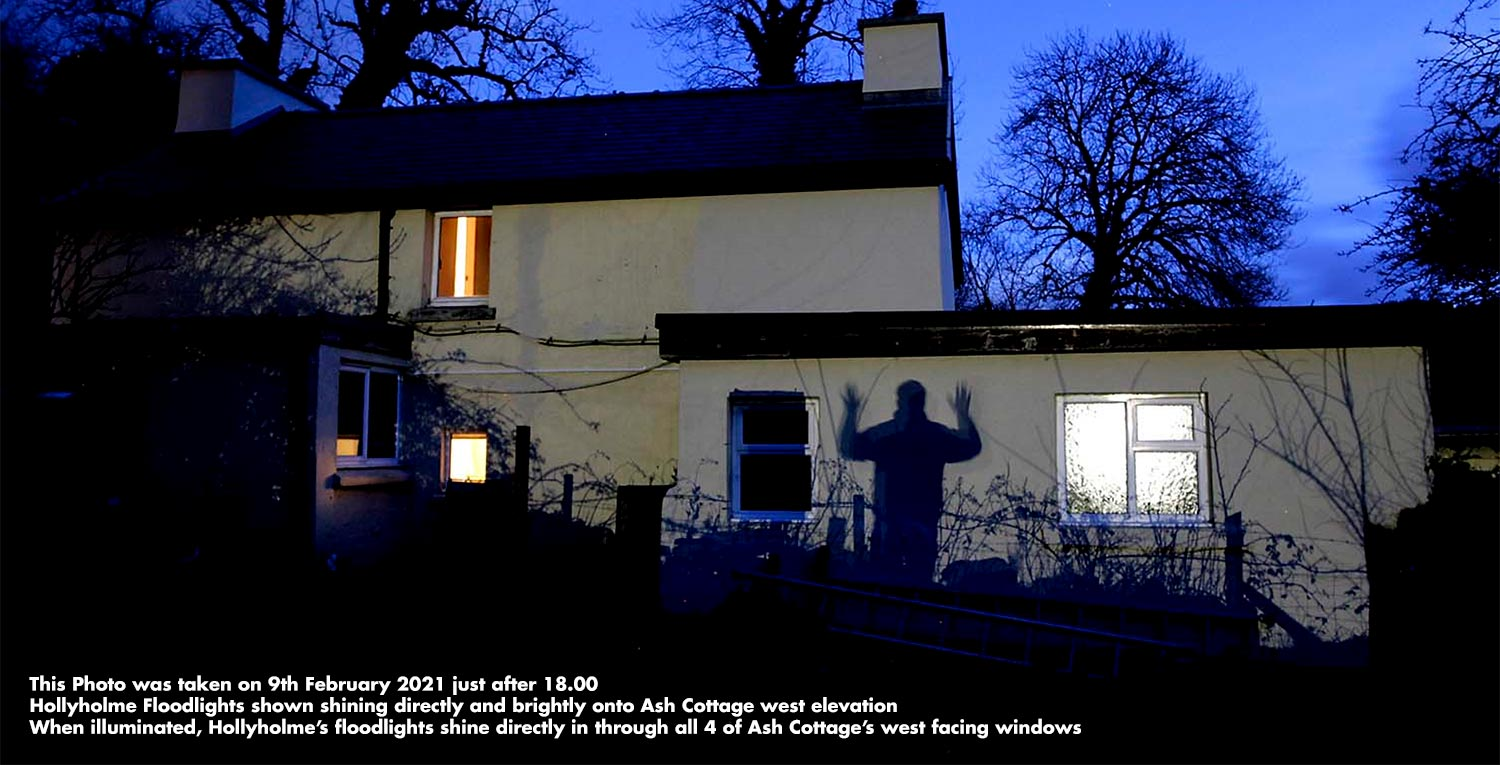 Hollyholme floodlights shown shining directly and brightly onto Ash Cottage west elevation. When illuminated, Hollyholme's floodlights shine directly in through all 4 of Ash Cottage's west facing windows. They are so bright that you can read a newspaper by their light